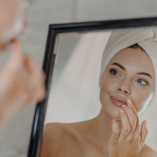 Healthy woman wears minimal makeup, takes care of complexion and lips, looks at herself in mirror, stands bare shoulders, wears bath towel on head, has healthy flawless skin. Beauty, hygiene concept